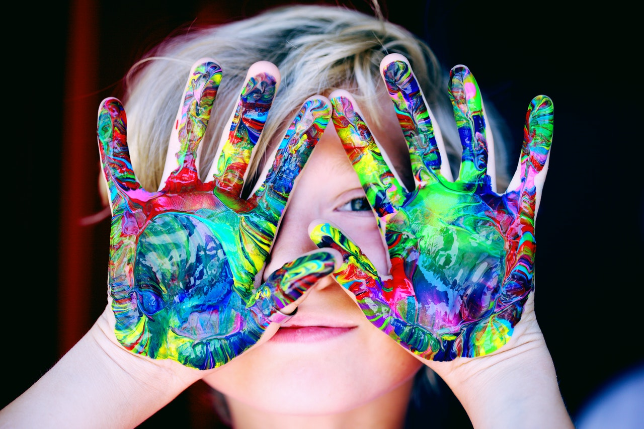 Kid hands are full of colors after painting